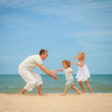 Happy family playing at the beach Stock Images