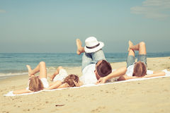 Happy family playing on the beach at the day time. Stock Photos