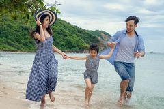 Happy family playing on the beach at the day time Stock Photo