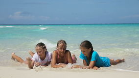 Happy family playing on the beach at the day time. Young family with two girls resting at beach in sunny day.mother and her two daughters lie on a tropical beach stock footage