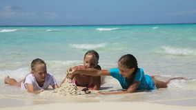 Happy family playing on the beach at the day time. Young family with two girls resting at beach in sunny day.mother and her two daughters lie on a tropical beach stock video footage