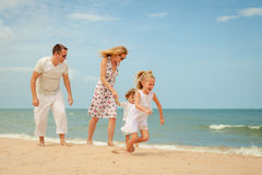 Happy family playing at the beach Stock Photos