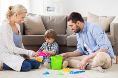 Happy family playing with beach toys at home. Family and people concept - happy little boy and parents playing with beach sand toys set at home Royalty Free Stock Images