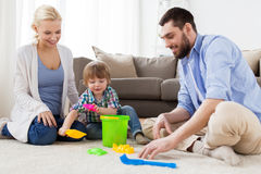 Happy family playing with beach toys at home. Family and people concept - happy little boy and parents playing with beach sand toys set at home Stock Photo