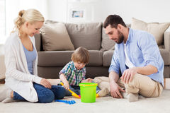 Happy family playing with beach toys at home. Family and people concept - happy little boy and parents playing with beach sand toys set at home Stock Image