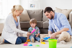 Happy family playing with beach toys at home. Family and people concept - happy little boy and parents playing with beach sand toys set at home Stock Photos