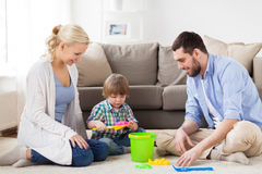 Happy family playing with beach toys at home. Family and people concept - happy little boy and parents playing with beach sand toys set at home Stock Photography