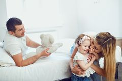 Happy family playing on the bed in the room royalty free stock images