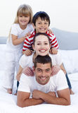 Happy family playing in bed together Royalty Free Stock Photography