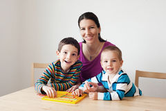 Happy family playing a board game. Children sitting at the table with their mother  playing the game Royalty Free Stock Image
