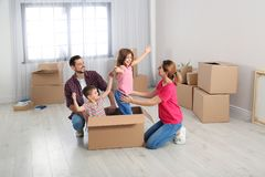 Happy family playing with cardboard box in their house. Moving day stock photos