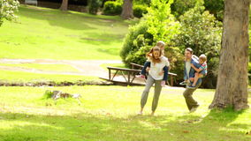 Happy family playing chasing in the park together