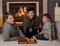 Happy family playing chess. At home in a cold winter day, looking at camera, smiling stock photo