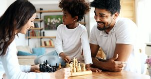 Happy family playing chess together at home stock photos