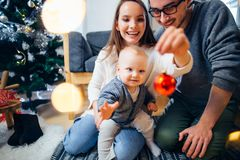 Happy family playing with Christmas balls at home. Happy family and little son playing home on Christmas holidays. New Year`s holidays. Toddler with mom and dad Stock Images