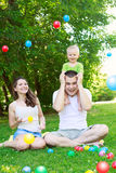 Happy family  playing with colorful balls in park Stock Photo