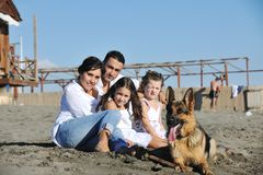 Happy family playing with dog on beach Stock Images