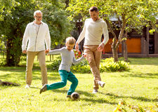 Happy family playing football outdoors Royalty Free Stock Photo