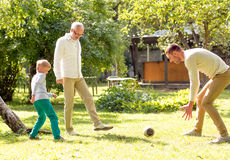 Happy family playing football outdoors Stock Photo