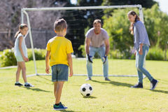 Happy family playing football in the park Stock Photos
