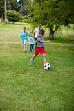 Happy family playing football in park Stock Photo