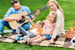 Happy family playing guitar and sitting together on plaid. At picnic royalty free stock photography