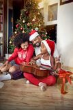 Happy family playing guitar songs in front of a decorated Christmas tree. At home stock photo