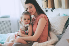 Happy family playing at home. Mother and toddler daughter relaxing and having fun in bed Stock Image