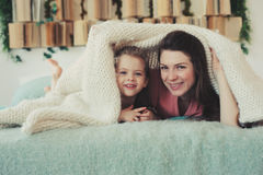 Happy family playing at home. Mother and toddler daughter relaxing and having fun in bed Royalty Free Stock Photography