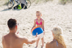 Happy family playing with inflatable ball on beach Royalty Free Stock Photos