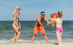 Happy family playing with inflatable ball on beach Royalty Free Stock Image