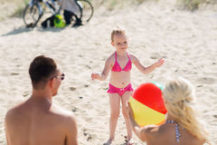 Happy family playing with inflatable ball on beach Royalty Free Stock Photo