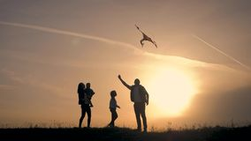 Happy family playing with a kite while on meadow, sunset, in summer day. Funny family time. stock video footage