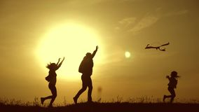 Happy family playing with a kite while on meadow, sunset, in summer day. Funny family time. Happy little girl launch a. Kite with parents. Mom, Dad and daughter stock footage