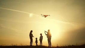 Happy family playing with a kite while on meadow, sunset, in summer day. Funny family time. Happy little girl launch a. Kite with parents. Mom, Dad and daughter stock video