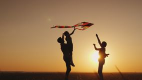 Summer activity - the family plays carefree with a kite. Happy family playing with a kite at sunset. Mom, Dad and daughter are happy together stock photography