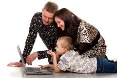 Happy family playing with laptop Stock Images