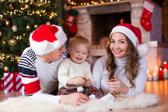 Happy family playing with little son lying near Stock Photos