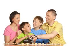 Happy family playing lotto. Portrait of happy family of four people playing lotto sitting at table Stock Photo