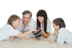Happy family  playing lotto. Portrait of happy family of four people playing lotto on a white background Stock Photography