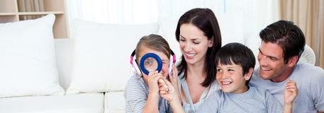 Happy family playing with a magnifying glass. In the living-room Stock Images