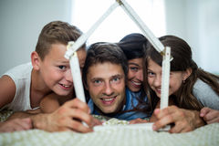 Happy family playing with model house in bedroom Stock Photo
