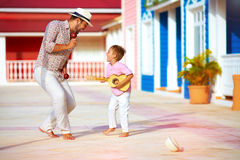 Happy family playing music and dancing on caribbean street Stock Photography