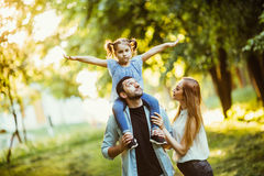Happy family playing in nature late afternoon sunlight in the fall, summer. Mother, father and daughter playing on the grass in th. E park Royalty Free Stock Images