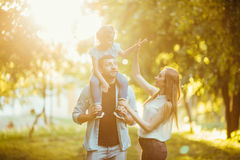 Happy family playing in nature late afternoon sunlight in the fall, summer. Mother, father and daughter playing on the grass in th. E park Stock Photo