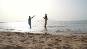 Happy family playing in the ocean and splashing water - Tourists on vacation on a tropical island.  stock video footage
