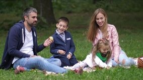 Happy family playing outdoors in autumn park. Dolly shot. 4k. Slow motion.