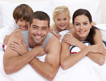 Happy family playing in parent's bed. Happy young family playing in parent's bed Royalty Free Stock Images