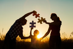 Happy family playing at the park at the sunset time. Royalty Free Stock Image