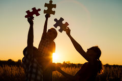 Happy family playing at the park at the sunset time. Stock Photography